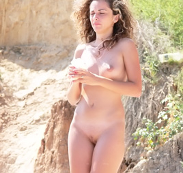 Her long slim nude body looks great in the sun