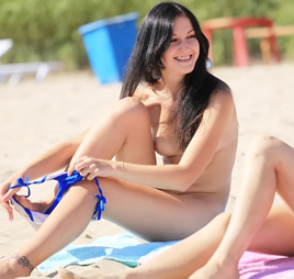 Naked body curvy teen bares all at a nudist beach in the sun