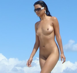 Young nudist shows off her slim body at the beach